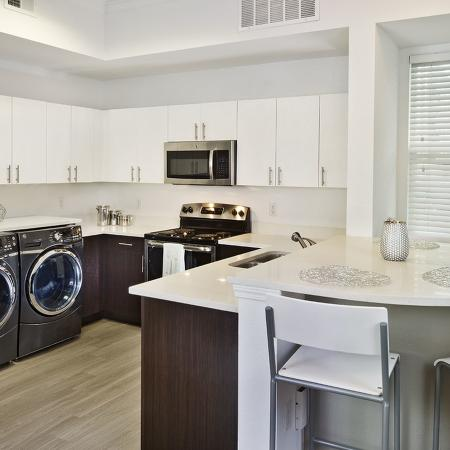 Kitchen with wood styled flooring, round breakfast bar with four chairs, white cabinets, stainless steel refrigerator, washer and dryer.