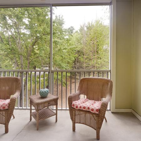 Screen patio with small table and chairs overlooking a pond.