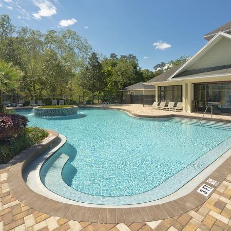 Community pool with landscaping and small palm on the left, leasing office on the right.