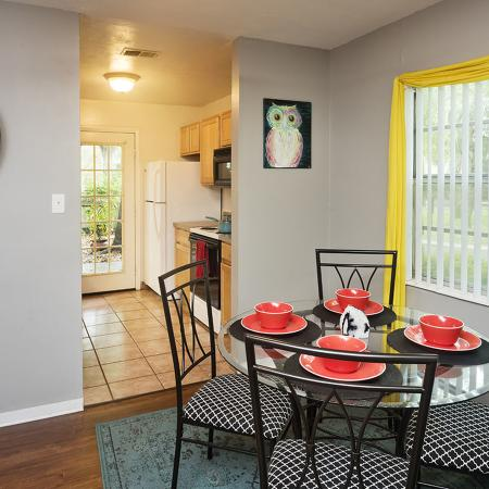 Dining area with small, circular, glass table four chairs and four place settings.  Window with blinds open and lined with yellow window dressing.  Opening to kitchen in the background.