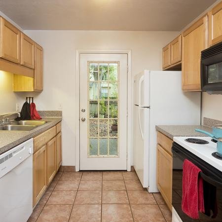 Galley style kitchen with tile floor, white appliances, and double sink.
