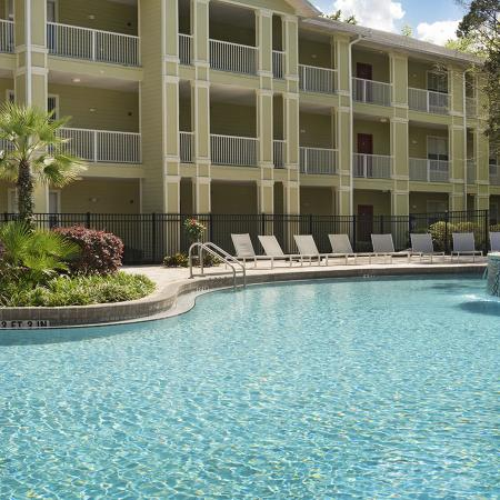 Community pool with landscaping, lounge chairs, fence, and three floor apartment building in background.