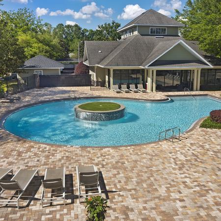 Community pool surrounded by lounge chairs and pavers.  Trees and leasing office in background.
