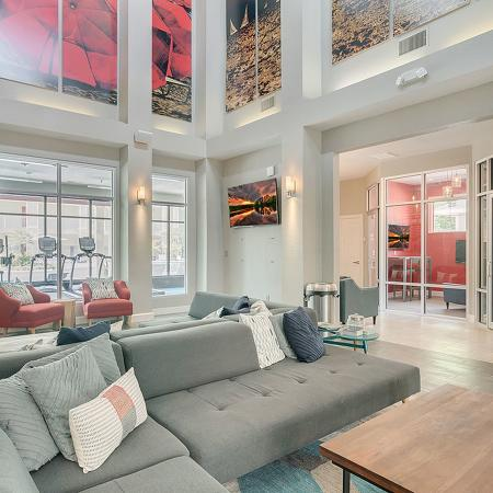 Community clubhouse with wood style tile, modern sectional couch, wood coffee table, tall ceiling with colorful banners hanging down.