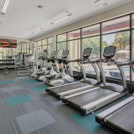 Fitness center with various treadmills, stationary bikes, elliptical, ceiling mounted television, all overlooking the pool.