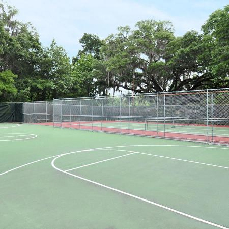 Full size basketball court with fenced in with trees surrounding it.  Tennis court in background..