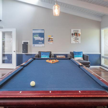 Community game room with pool table chairs and entrance in background.