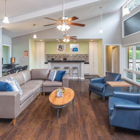 Community clubhouse with wood style flooring, modern furniture and lighting.  Bar area in background.  Double doors leading to the pool on the right.