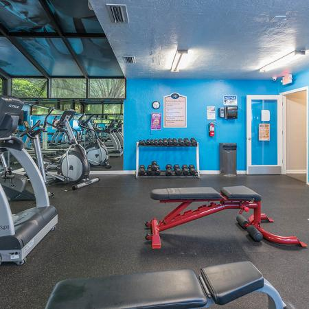 Community fitness center with various exercise equipment and free weights.