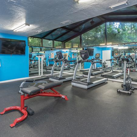 Fitness center with various cardio equipment and wall mounted television.  Mirrored wall in the background.