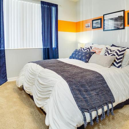 Carpeted bedroom with blue curtains and a horizontal orange stripe along both walls.  Bed is made with white bedspread and lots of pillows.