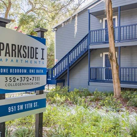 Parkside I (part of College Manor) monument sign surrounded by landscaping and an apartment building in the background.