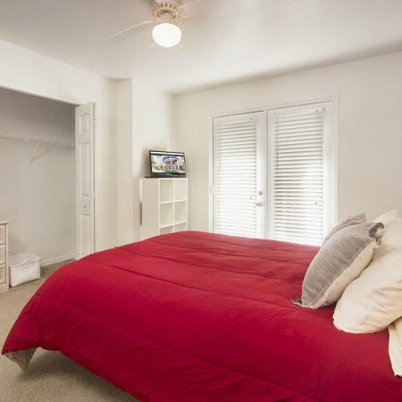 Carpeted bedroom with closet doors open, exposing the shelf space inside.  Bed is made with red bedspread.  There is also a white shelf with a television on top, and double doors leading to the outside in the background.