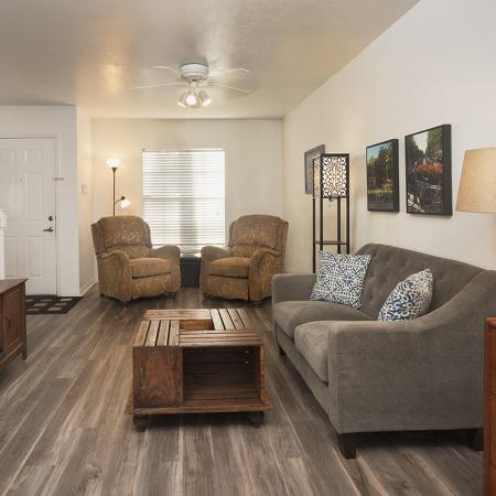 Living area facing front of apartment.  Shown here is the gray cloth couch, wooden coffee table and entertainment center, also two recliners, entrance to the apartment, and a window in the background.