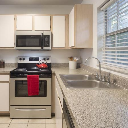 Galley style kitchen with stainless steel appliances, white cabinets, and a double sink..