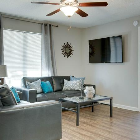 Living room with leather couch, love seat, glass coffee table, wall mounted television, and ceiling fan.