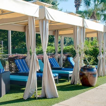 Four cabanas with lounge chairs underneath, and grass carpet.