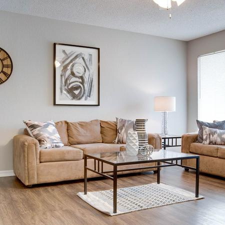 Living area with wood style flooring microfiber couch and loveseat, glass coffee table.