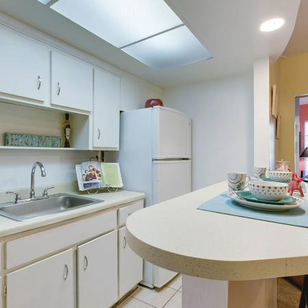 Close up of kitchen with white cabinets, white appliances, single tub sink, and breakfast bar with two place settings.