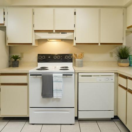 Kitchen with white appliances, beige cabinets, light tiled flooring.