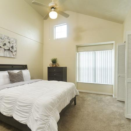 Beige carpeted bedroom with white comforter place on bed.  Folding closet door is open, exposing storage area.