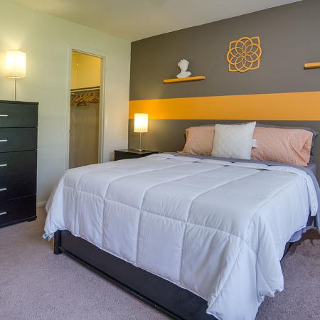 Bedroom with white colored comforter over bed.  Dark wooden dresser and cache green with mustard stripe accent wall.  Open closet in background.