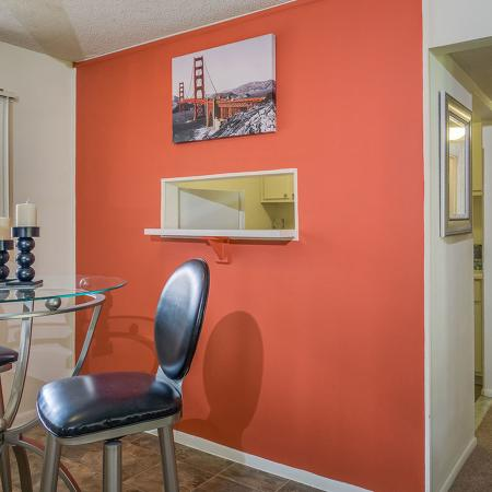 Dining area with high top dining table and chairs, orange accent wall, and hallway leading to other areas of the apartment.