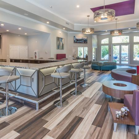 Community clubhouse with wood style flooring, modern furniture and lighting.