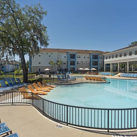 Large community pool lined with lounge chairs.  Covered basketball court and apartment building in background..