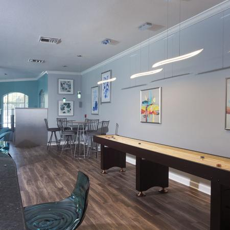 Community clubhouse with shuffleboard on the right, several wall mounted televisions on the left.  Art hanging from the walls.