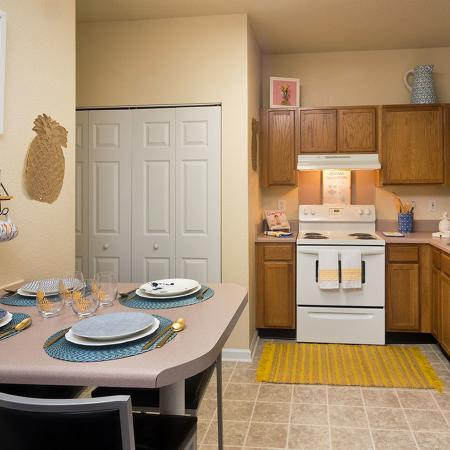 Kitchen with tile like floor, white appliances, tan colored cabinets, and small table with four place settings.