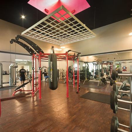 Community fitness center with wood styled floor, punching bag, and various exercise equipment.