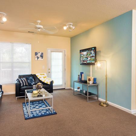 Brown carpeted living room with leather couch and love seat, glass coffee table, entertainment center below and wall mounted television.  Blue accent wall on the left side of the room.