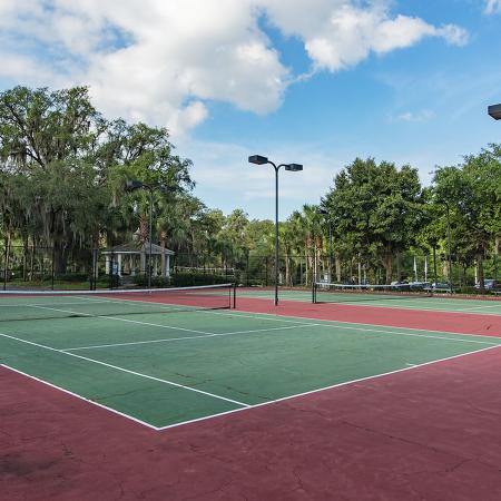 Two red and green tennis courts with trees in background.
