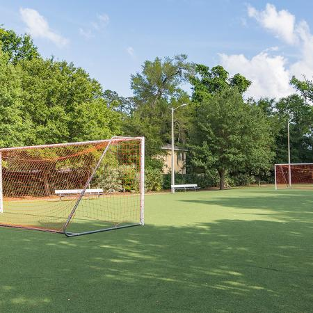 Large green space with two soccer goals facing each other.