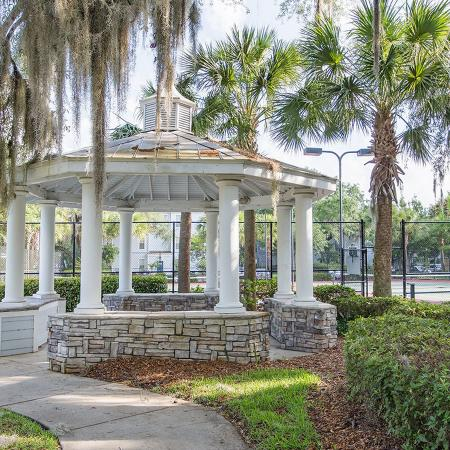 White pillared gazebo surrounded by tall oak trees and lush landscaping.  Tall page link fence in background.