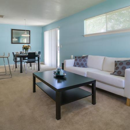 Carpeted living room area with light blue accent wall, white couch and chair, and wooden coffee table.  Dining area and table in the background.