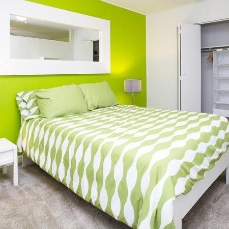 Carpeted bedroom with green accent wall, green bedspread, two white end tables with lamps, and a double doored closet that is open.