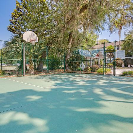 Half basket ball court enclosed in fence.