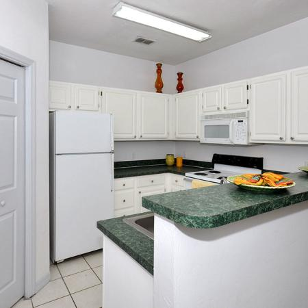 Kitchen with white cabinets, white appliances, tile floor.