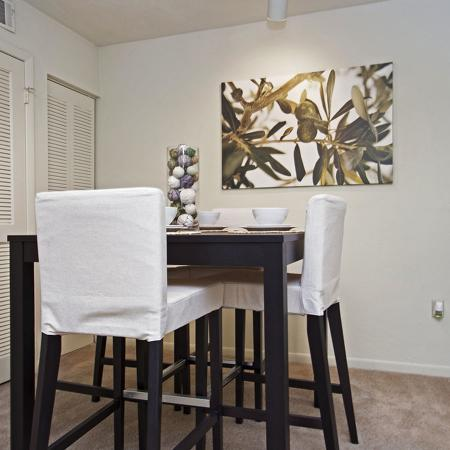 Dining room with tall table and chairs.  Chairs are covered with white chair covers.