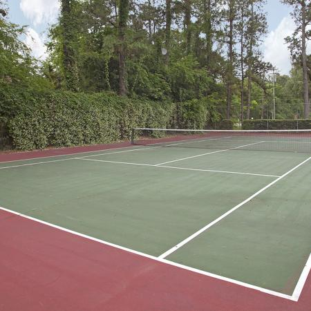 Red and green tennis court surrounded by fence, bushes and trees.
