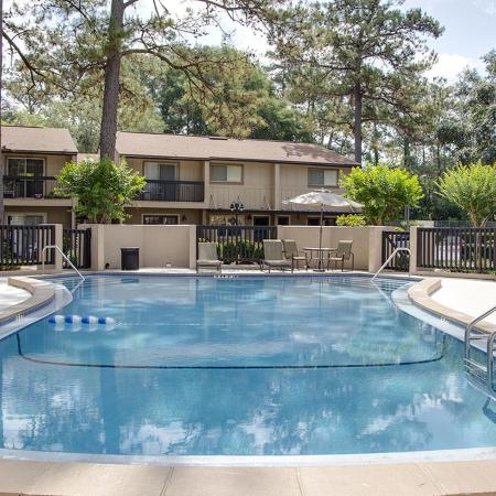 Rectangular community pool with with tan privacy wall, apartment building and pine trees in background.