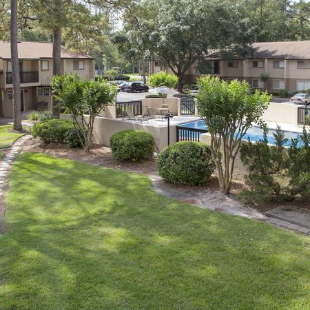 Panoramic photo of a narrow walkway surrounded by green grass, trees, landscaping.  Pool and apartment buildings in the distance.