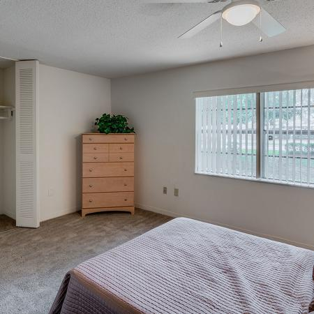 Large bedroom with open closet doors, dresser, lamp and ceiling fan.