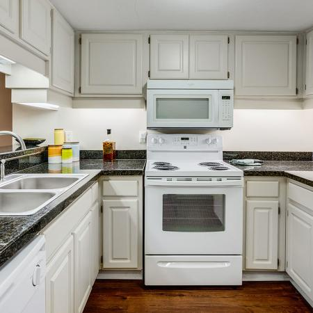 Light colored kitchen with white appliances and double sink.