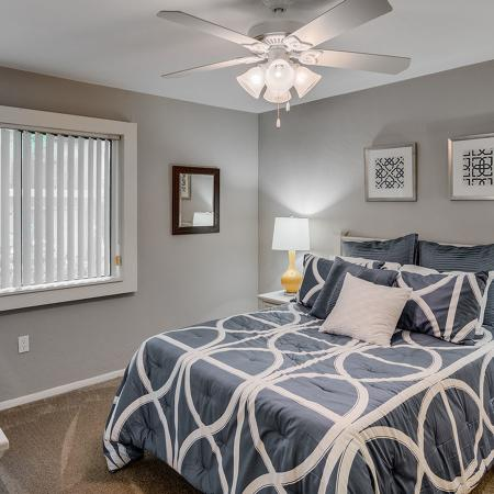 Bedroom with bed, ceiling fan, dresser and night stand.