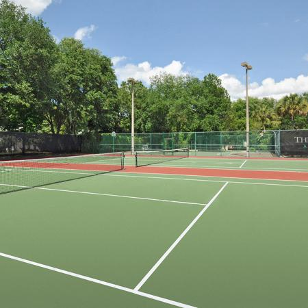 Two tennis courts with trees and sign in background.