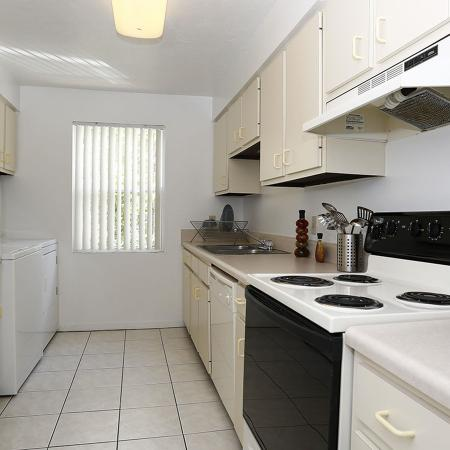 Galley style kitchen with light colored tile, light colored cabinets, and mixed appliances.