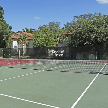 Green and red tennis court with fence in background holding up a banner with the Biven's Cove logo on it.  Trees and buildings in the distance.